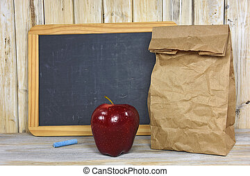 paper bag and red apple - Brown paper bag and red apple with...