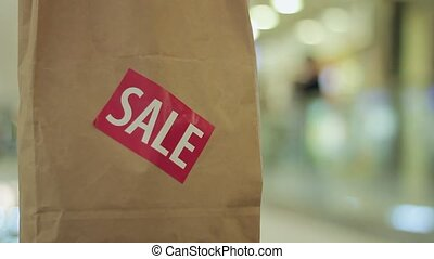 Brown paper bag with red sale sticker on it in shopping mall Close up
