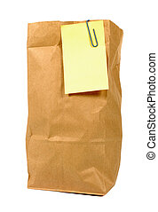 Brown paper lunch bag with yellow sticky note