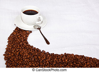 Brown path of coffee beans leading to a cup of black coffee