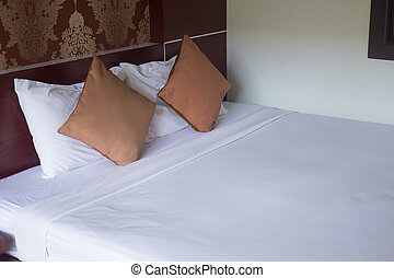 Brown pillows on bed in classic bedroom