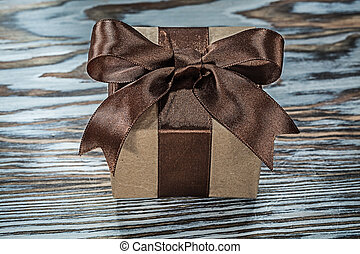 Brown present box with tied bow on wooden background