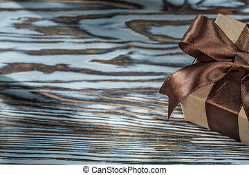Brown present box with tied ribbon on wooden background