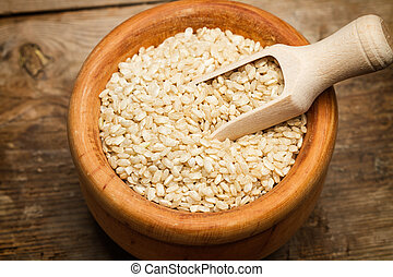 Brown raw rice in a wooden bowl