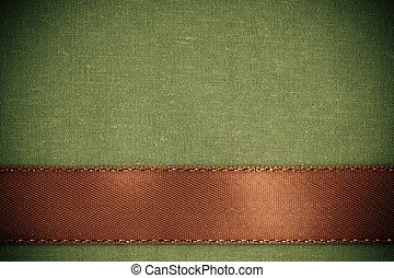 Brown ribbon on green fabric background with copy space.