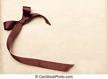 Brown ribbon over vintage gift old paper background
