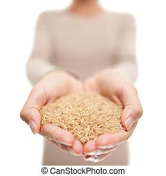 Brown rice grains natural food closeup in open hands. Woman showing uncooked raw rice grain in studio