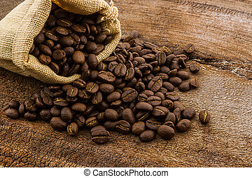 Brown roasted coffee beans in canvas sack.