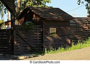 brown rural wooden fence and shed with a window outside