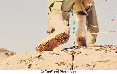 Brown Shoes of a Boy Scout Climbing a Rock