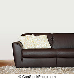 Part of brown leather sofa with pillows
