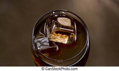 Brown soft drink with ice in glass. Top view