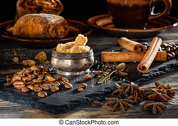 Brown sugar, coffee grains and sticks of cinnamon on a black...