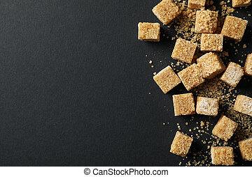 Brown sugar cubes on black background, top view