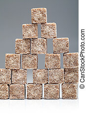 Brown sugar cubes stacked up on grey background