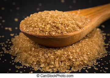 Brown sugar in wooden spoon on dark background