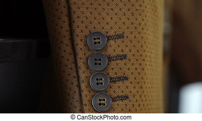 Brown suit jacket sleeve with buttons closeup. Man's fashion...