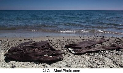 Brown suit lay on sand near water at sunny day, seascape at...