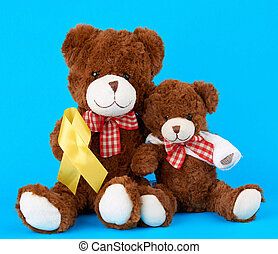 brown teddy bear sits and holds in his paw a yellow silk ribbon on a blue background, concept of the fight against childhood cancer