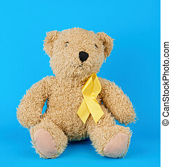 brown teddy bear sits and holds in his paw a yellow silk ribbon on a blue background