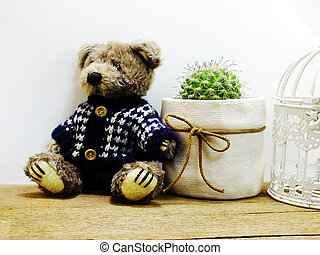 brown teddy bear sitting on wooden table with cactus in small pot and space copy