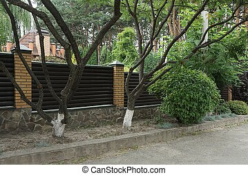 brown wall of a fence made of wooden boards and bricks on the street