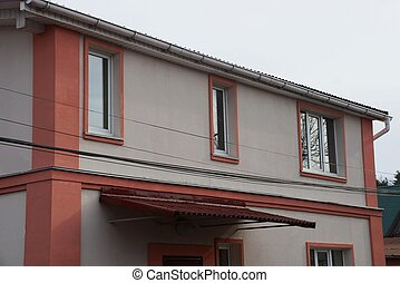 brown wall of a private house with windows on the street