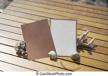 Brown - White card on the wood table decorate by shell, coral.