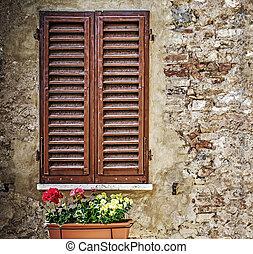 brown window shutters in a rustic wall