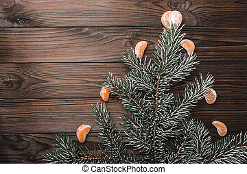 Brown wood background. Fir tree fir tree, adorned with slices of mandarin. Christmas greeting card and new year. Xmas and Happy New Year composition. Flat lay, top view