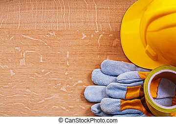 Brown wood board with safety tape protective gloves and hard hat