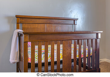 Brown wooden baby crib with blanket