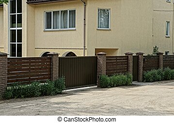 brown wooden fence and gate in the grass near the road near a large house with windows