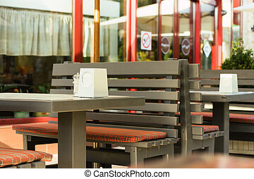 Brown wooden tables in a cafe outdoors in the summer