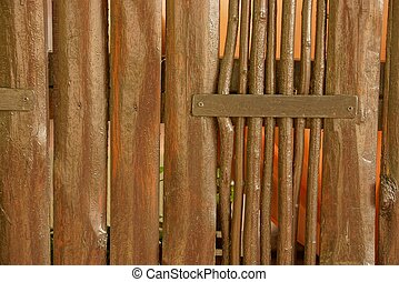 brown wooden texture of planks and branches in the wall of a rural fence