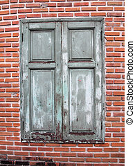 Brown wooden window on brick wall