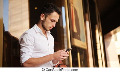 . Brownhaired young male scrolling on his mobile phone