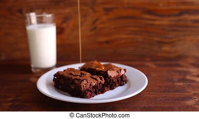 Brownie on a plate, on a wooden texture. Watered sweet salty...