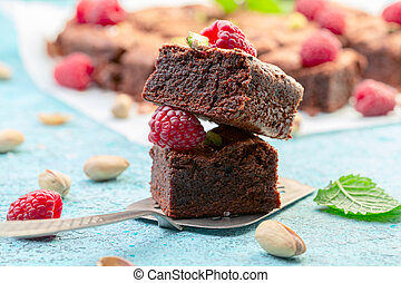 Brownie slices with raspberries and pistachios.