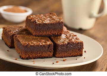 Freshly baked brownie pieces on a plate with cup in the back (Selective Focus, Focus on the left front part of the upper brownie)