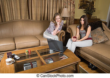 Browsing from home - Two attractive women sitting on beige...