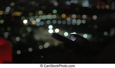 Browsing on smart phone at night, city lights in background