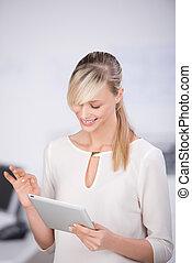 Long hair female browsing the internet through digital tablet