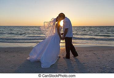 bruid en bruidegom, echtpaar, zonsondergang strand, trouwfeest