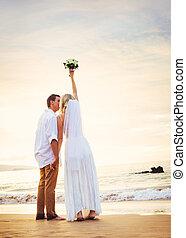 bruid en bruidegom, schouwend, ondergaande zon , op, mooi, tropisch strand, romantische, echtpaar