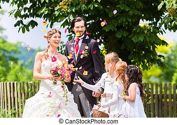 bruiloftspaar, en, bruidsmeisje, het overgieten, bloemen