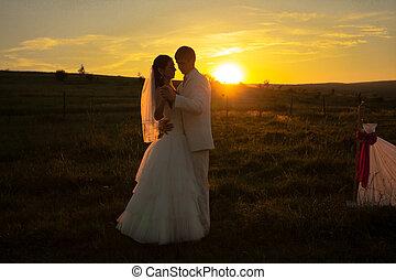 bruiloftspaar, op, ondergaande zon