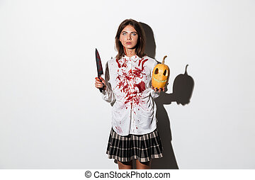 Bruised and bloody zombie woman holding large knife