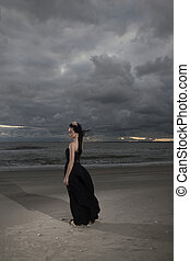 Brunete woman posing on seashore in black long dress