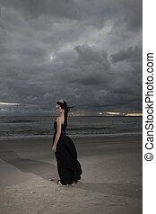 Brunete woman posing on seashore in black long dress